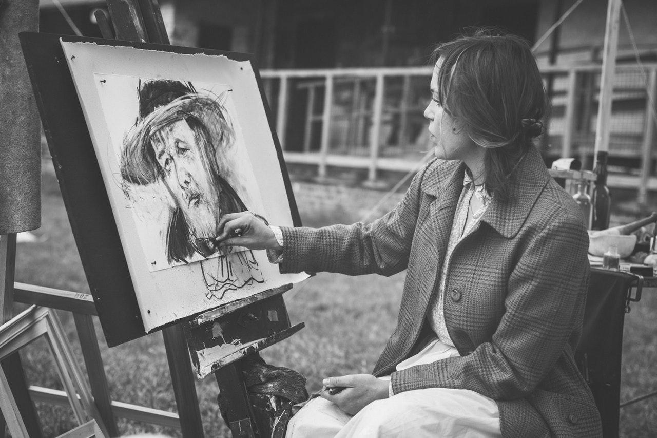 Mulher artista desenhando homem de chapéu